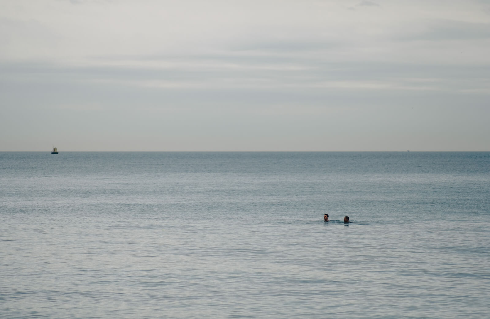 Two people swimming in Vouliagmeni in winter