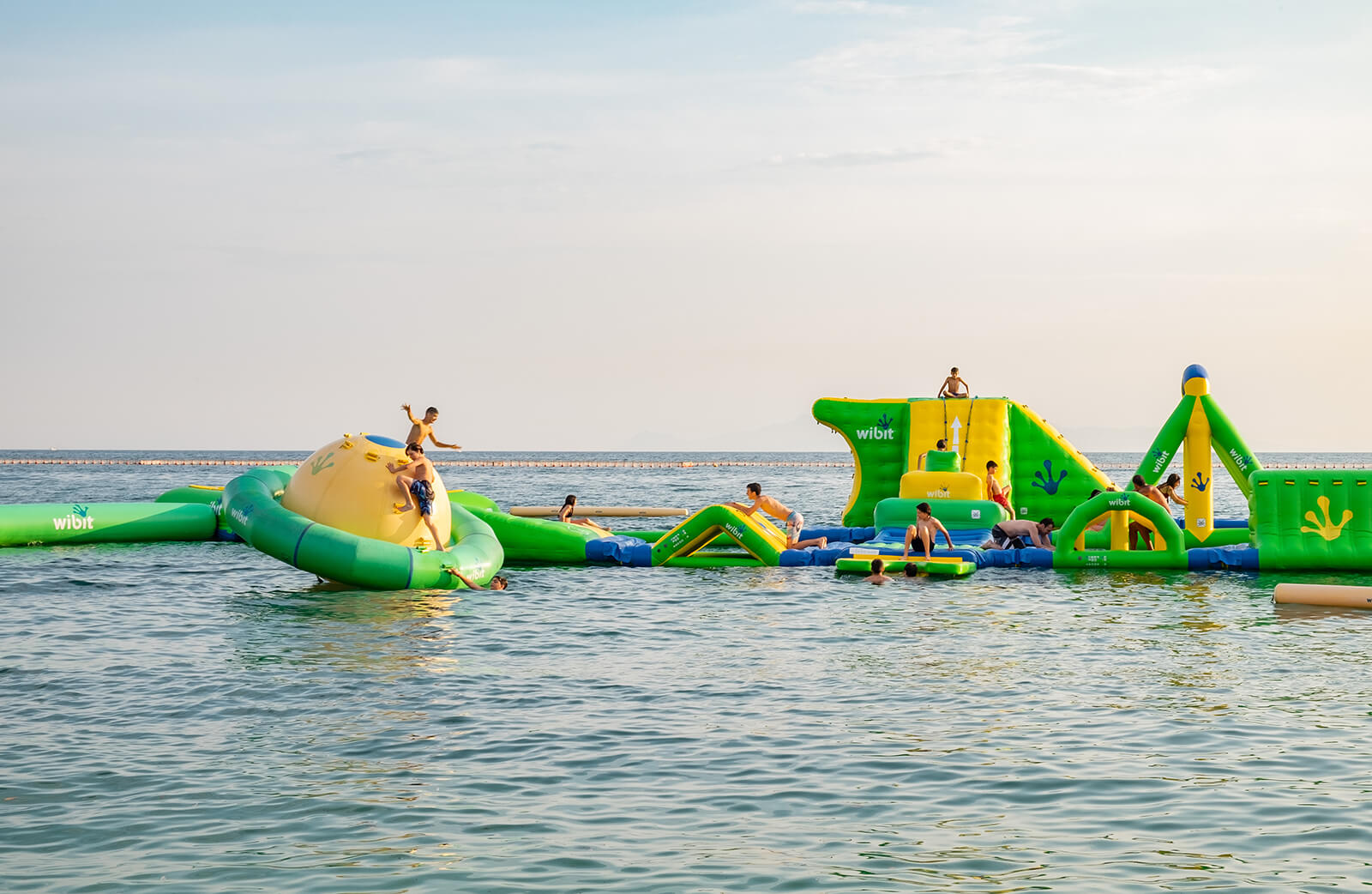 Children playing in the sea on a green and yellow floating playground