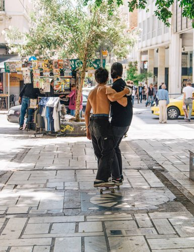 Two skaters on a skateboard on Aiolou Street, Athens