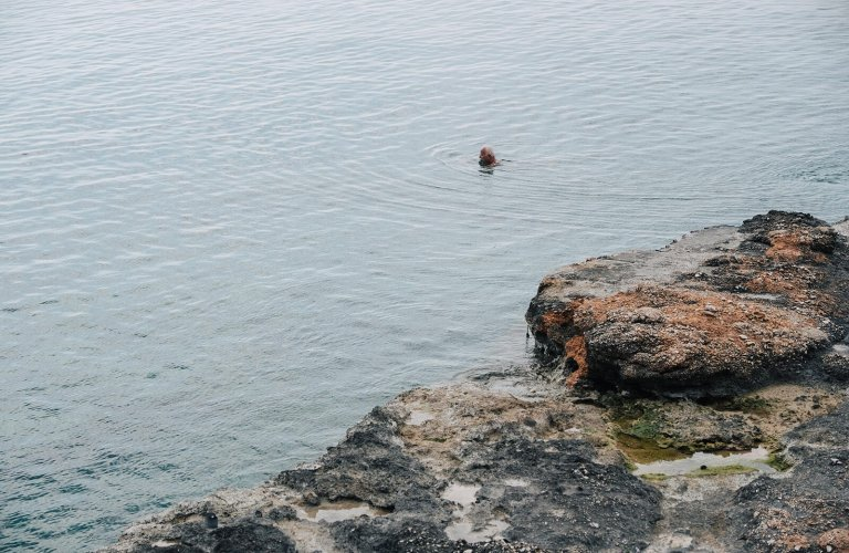 man swimming in winter in Vouliagmeni