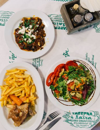 Plates of Greek food served on a table, french fries with lamb, green salad with tomatoe slices and smoked aubergines with feta cheese