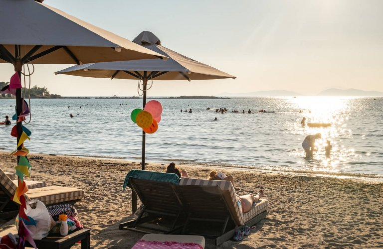people lying on beach chairs on a sandy beach in front of the sea at Balux, Glyfada