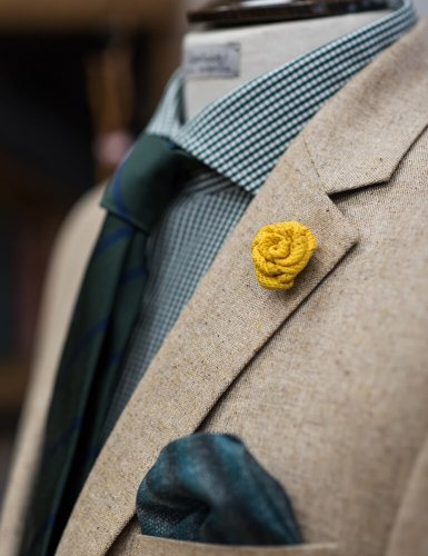 a men's jacket with a yellow flower brooch and a blue handkerchief