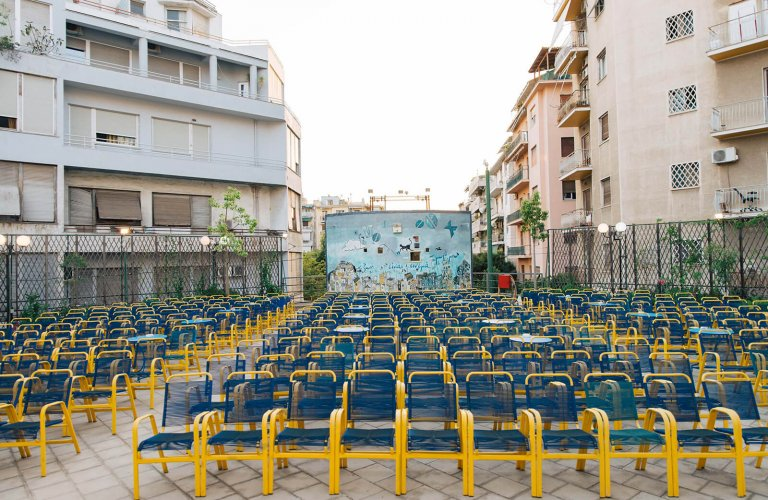 chairs and movie screen amidst apartment buildings.