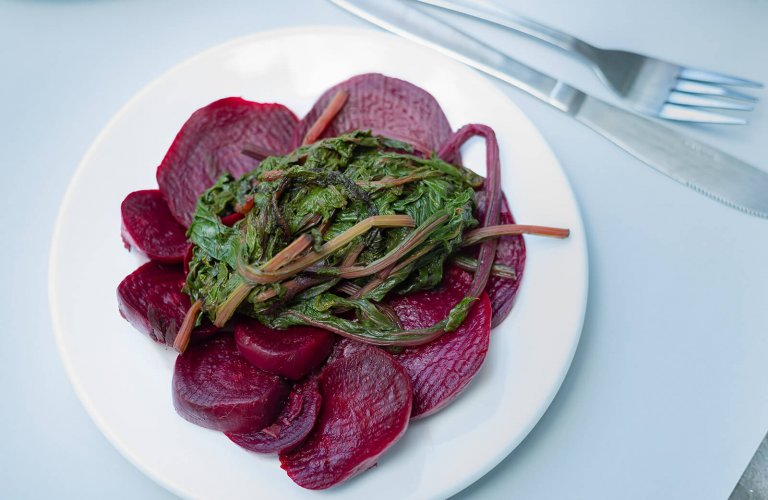 Sliced beetroots with their leaves on a white plate.