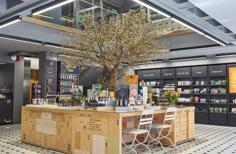 A wooden stall with two chairs and an olive tree coming out of its centre, in a store selling beauty products.