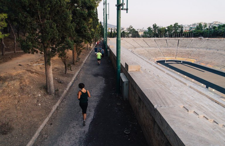 Woman running on a path next to an open marble stadium.