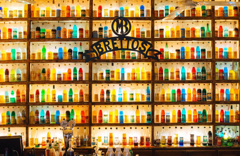 A wall with colourful liquor bottles at Brettos in Athens.