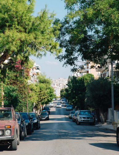 a street with parked cars and trees at Palio Faliro in Athens