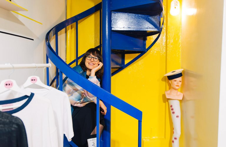 a smiling woman sitting on a yellow and blue staircase at Ode to Socks in Athens