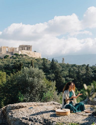 a woman sitting on a rock at Pnyx with a view of the Acropolis in Athens