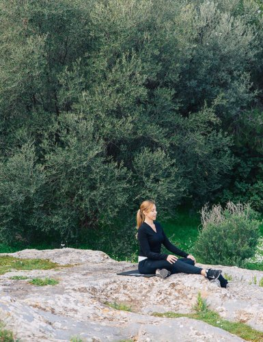a woman sitting on a rock in Pnyx Athens