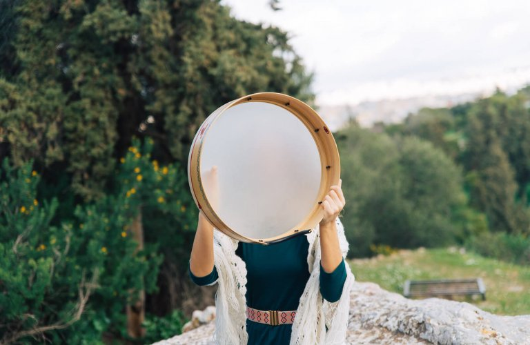 a woman holding a drum over her face in Pnyx Athens