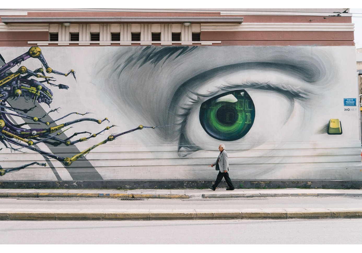 graffiti of a green eye on a wall and a person walking by.