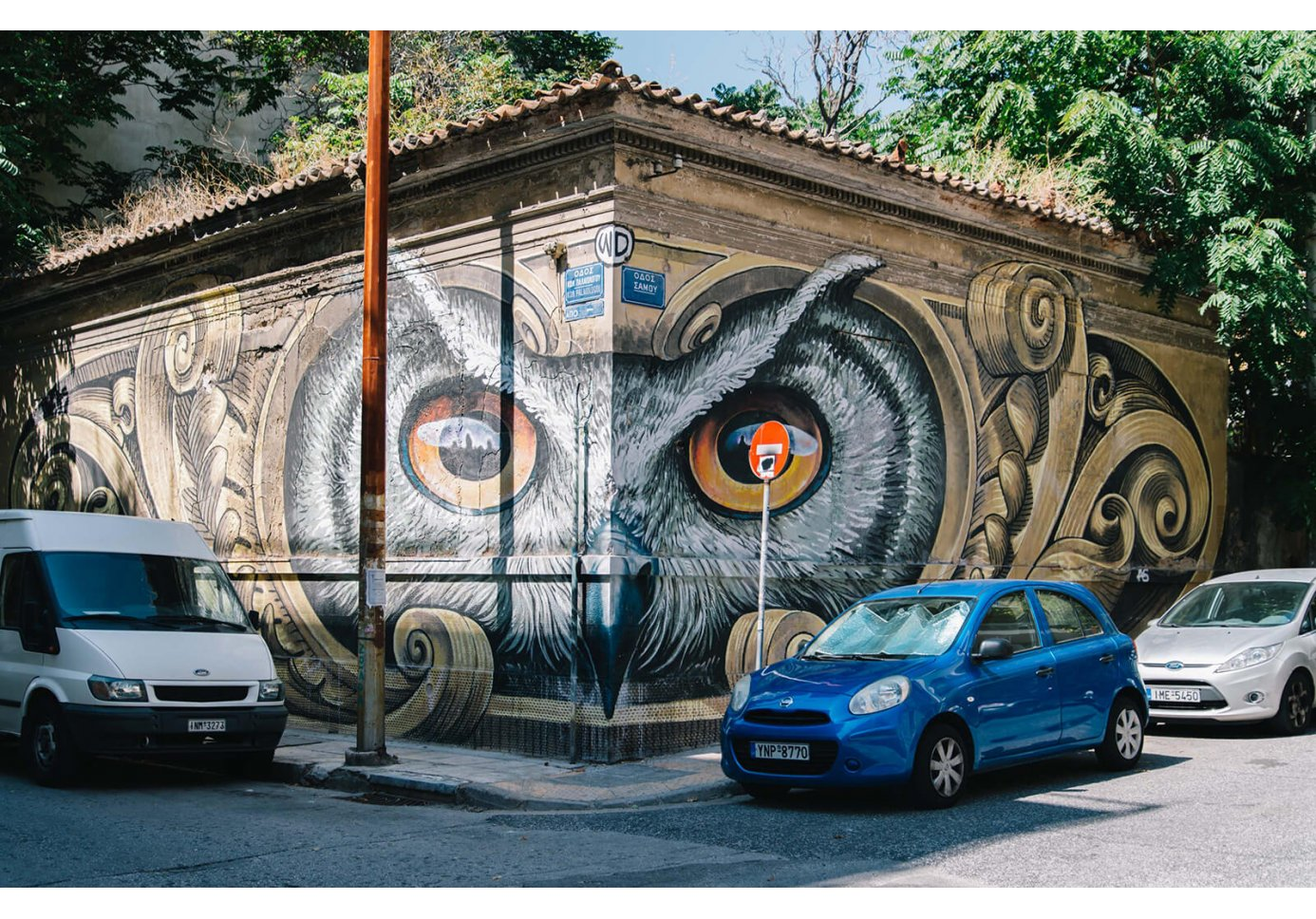 Graffiti of an owl's face on corner of two walls and 3 parked cars.
